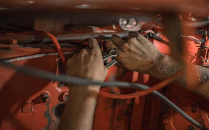 Ruke mehaničara dok popravlja kvar na automobilu