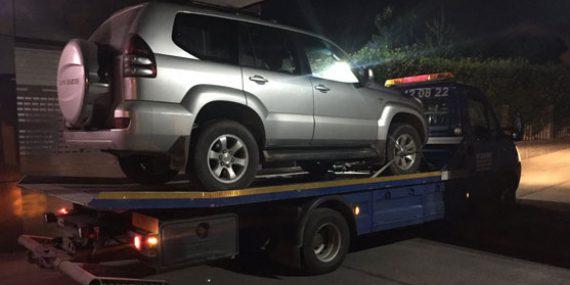 Šlepanje sivog džipa na šlep vozilu po noći