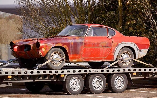 crveni automobil koji nije u voznom stanju na prikolici šlepa