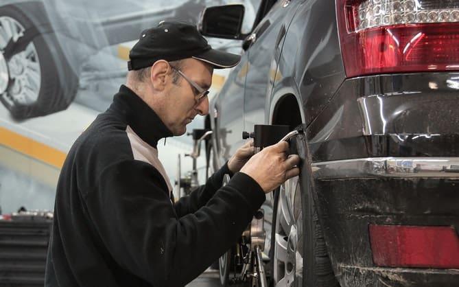automehaničar popravlja točak sivog automobila