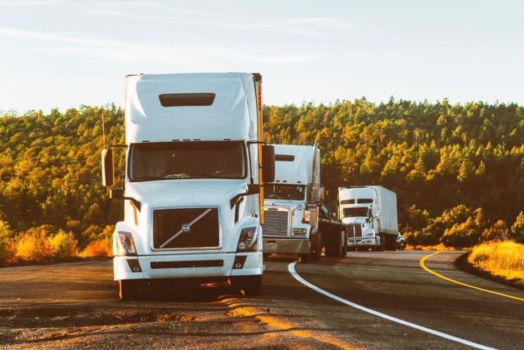 tri velika bela kamiona parkirana pored puta
